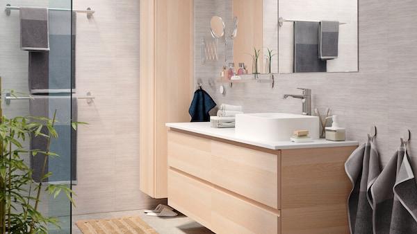 حمام مشرق وأنيق مع وحدة حوض غسل GODMORGON وخزانة GODMORGON مرتفعة بتأثير خشب البلوط المموج بالأبيض.