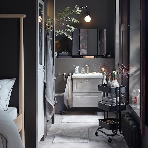حمام رمادي بالكامل مع وحدة حوض غسل وخزانة عالية بلون رمادي فاتح، وعربة سوداء والعديد من الزهور المجففة التزيينية.