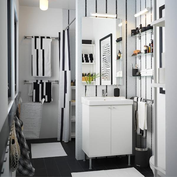 حمام صغير أبيض وأسود مع حوض غسيل أبيض ومناشف مقلمة وستارة دوش مقلمة.