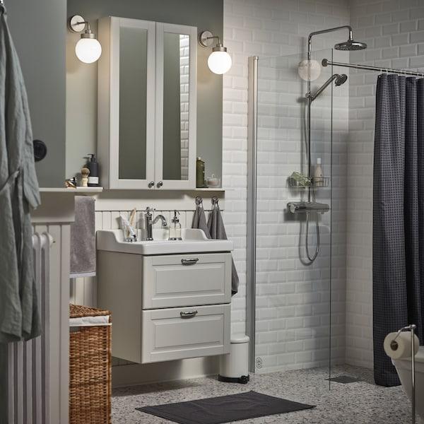 حمام صغير به خزانة مرآة بيضاء، ومغسلة حمام بلون رمادي، ودعاسة حمام بلون رمادي داكن وستارة للدوش بلون فحمي.