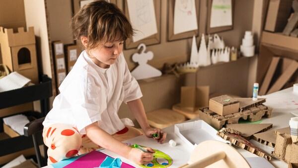 Hnedovlasé dievčatko, ktoré si kreslí v detskom kútiku a je pri tom obklopené kreatívnimi potrebami.