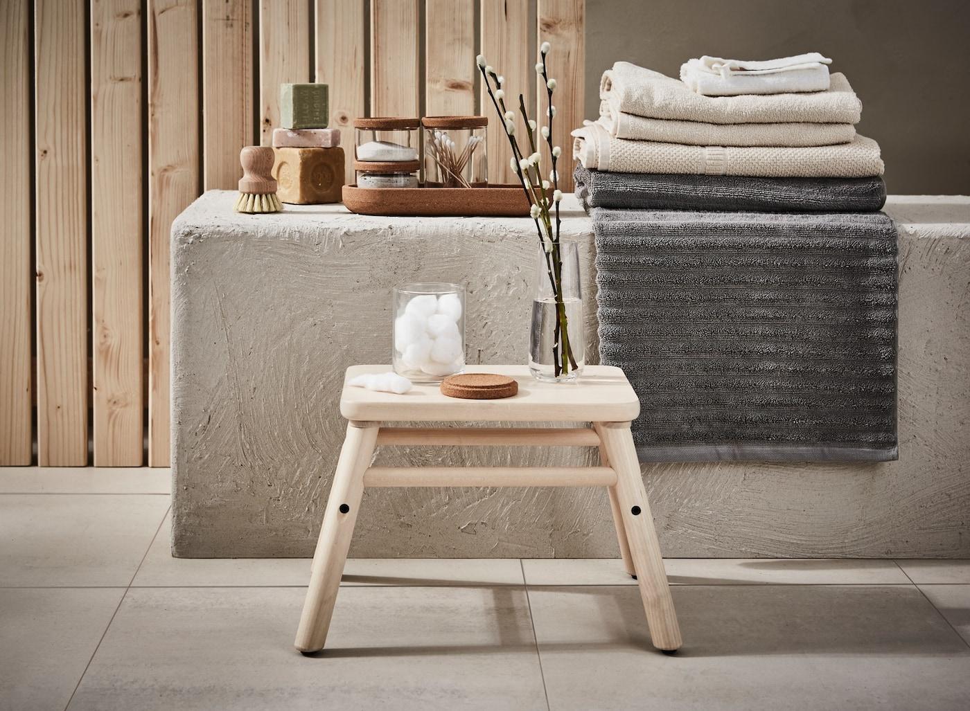 Hocker aus Holz vor einer Ablage mit beigen und grauen Handtüchern und Kleinaufbewahrung für das Badezimmer