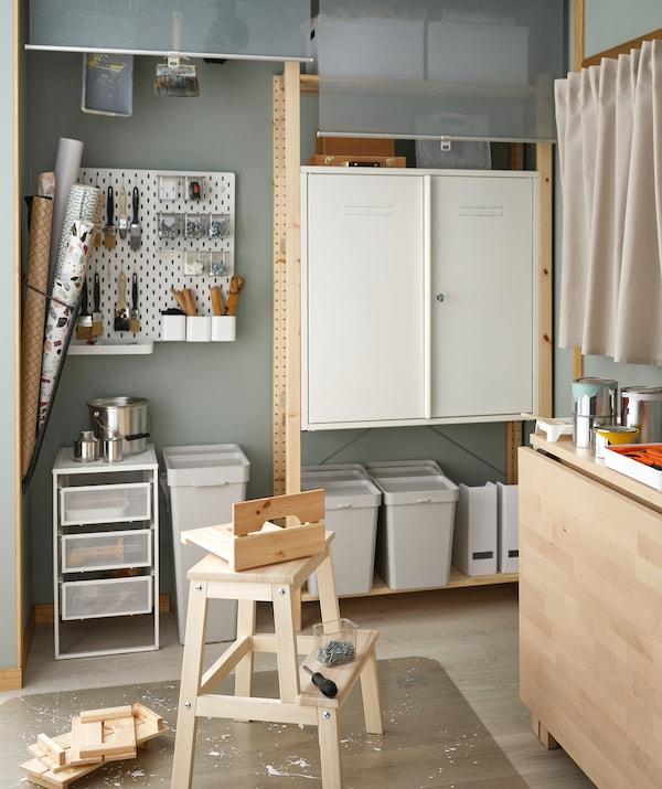 Hocker mit Tischlereizubehör auf einem KOLON Fussbodenschutz. An der Rückwand stehen IVAR Elemente mit Hobbybedarf darin.