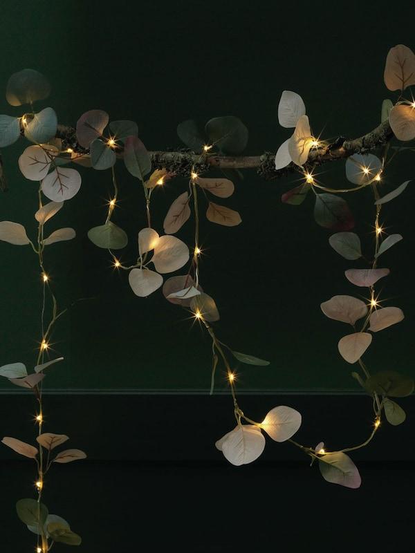 HÖSTPROMENAD battery operated LED eucalyptus green string lights in a nighttime setting