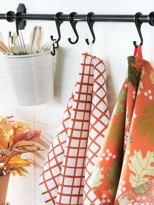 HÖSTPROMENAD orange patterned tea-towels hanging on kitchen wall rail