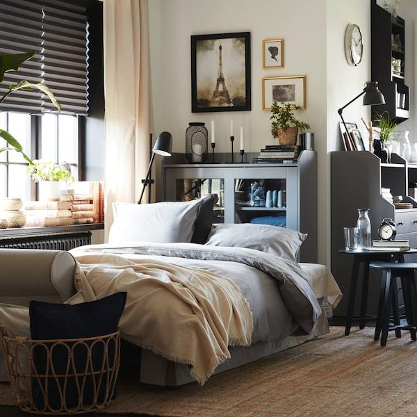 Hojně zdobený kout obývacího pokoje se světle béžovou rozkládací pohovkou, jutovým kobercem ašedou skříňkou sprosklenými dvířky HAUGA.