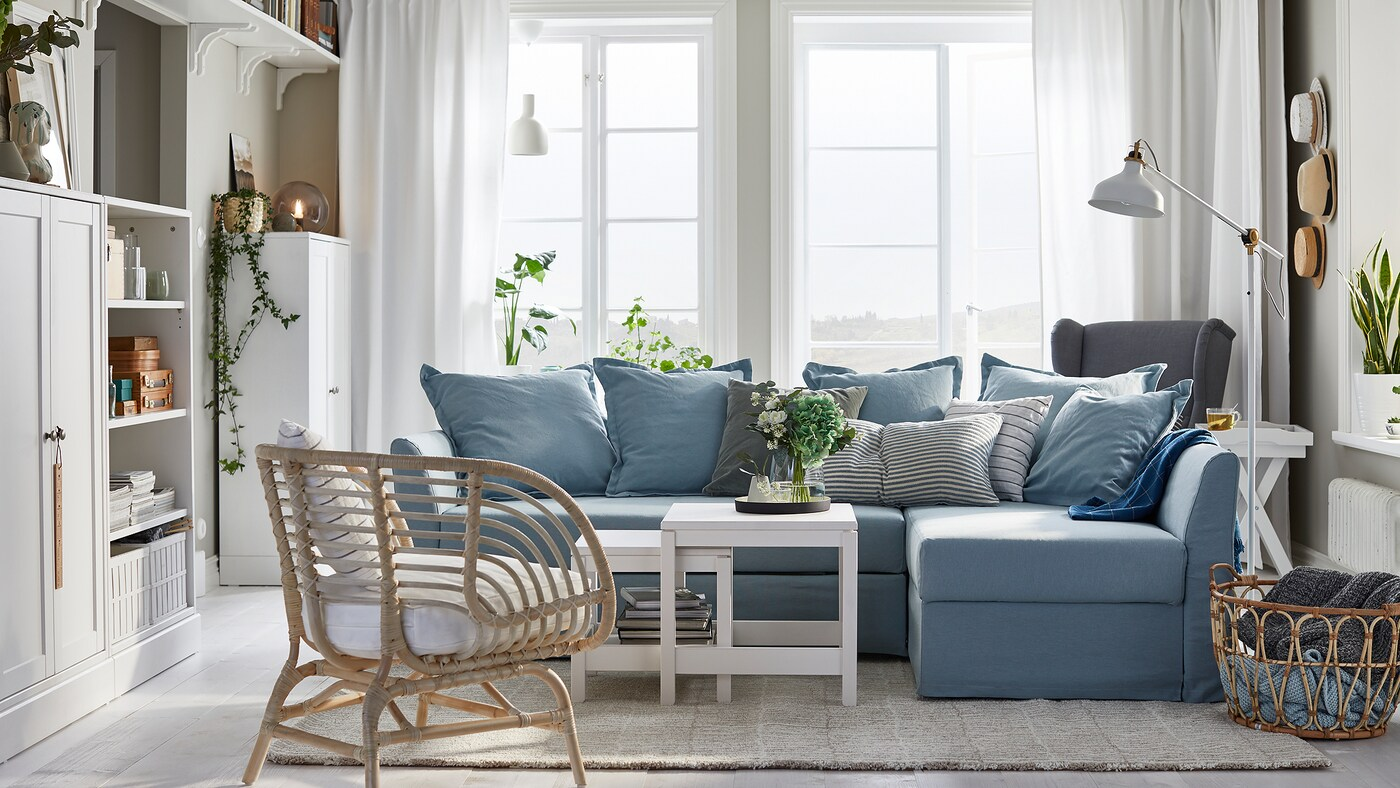 HOLMSUND light blue corner sofa-bed in a living room setting, with a rattan chair, white coffee tables and a large window.