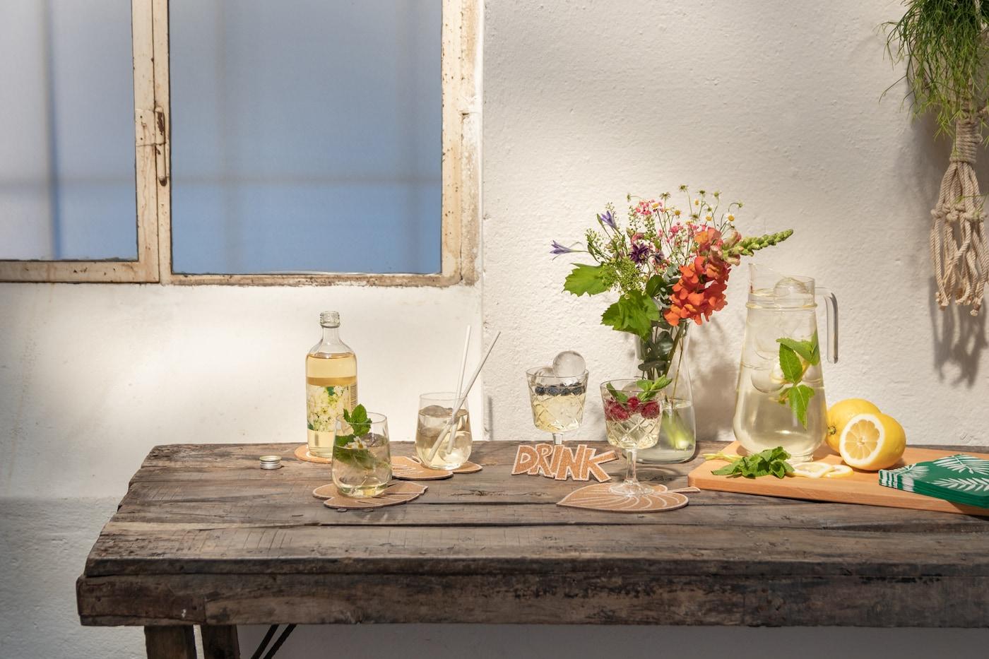 Holztisch mit Gläsern & Flaschen, die auf selbst gebastelten Korkuntersetzern stehen.