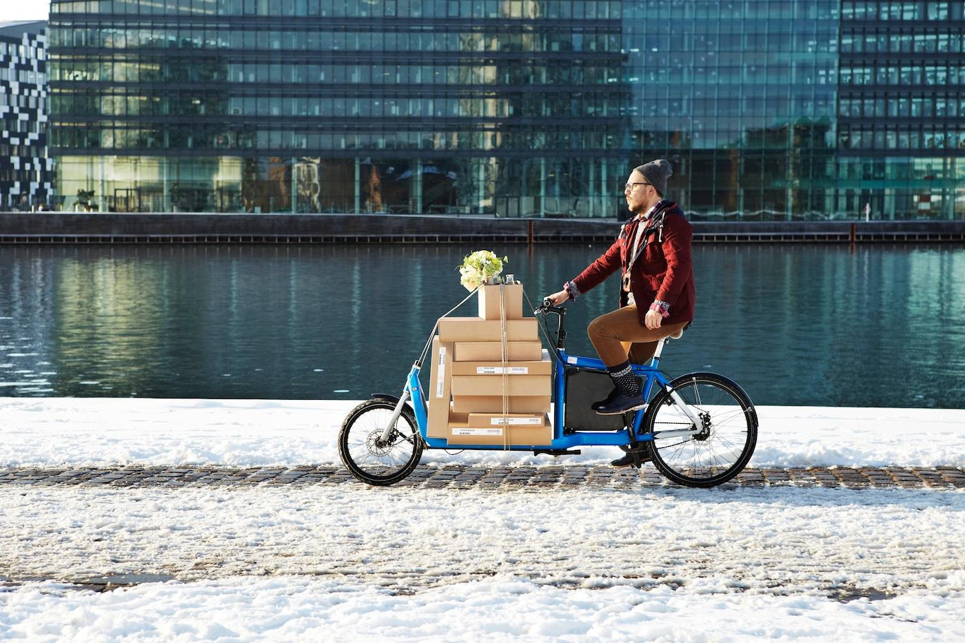Hombre abrigado andando en bicicleta, llevando sus cajas de empaque plano de IKEA. Va por una calle con nieve y al lado de un sector con agua y edificios.