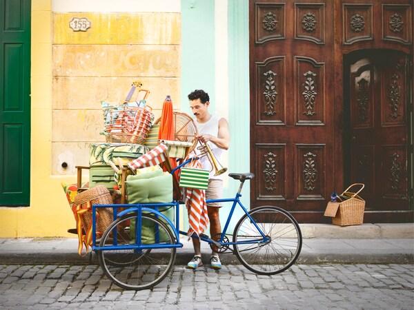 Hombre apilando productos de estilo playero en una bicicleta azul, colocada en una calle de adoquines gris.