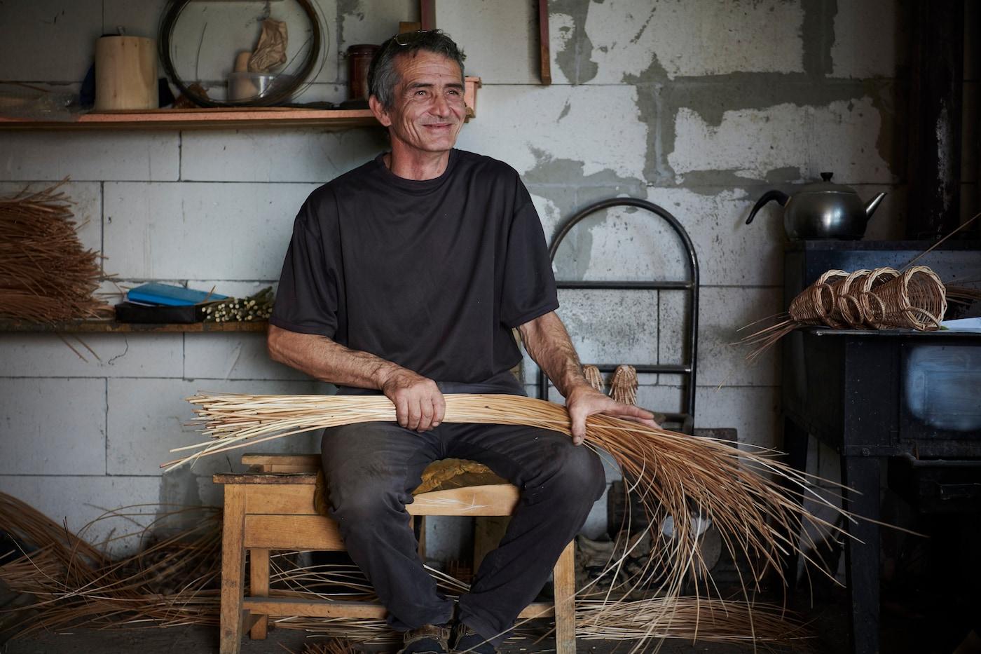 Hombre sentado con polera gris oscura, sosteniendo un material de fibra natural para armar un mueble.