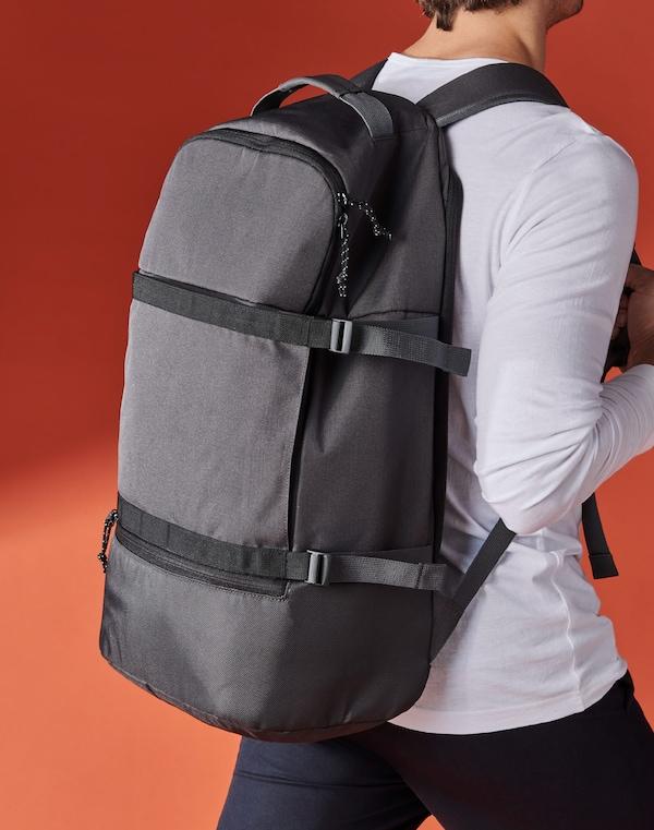 Home camiñando cunha mochila VÄRLDENS gris escura ás costas, que contrasta co fondo laranxa.