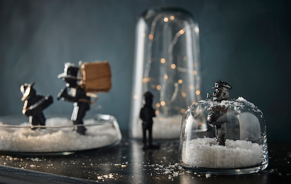 Home-made snow globes made using IKEA glass jars and vases, with lights, fake snow and figurines inside.