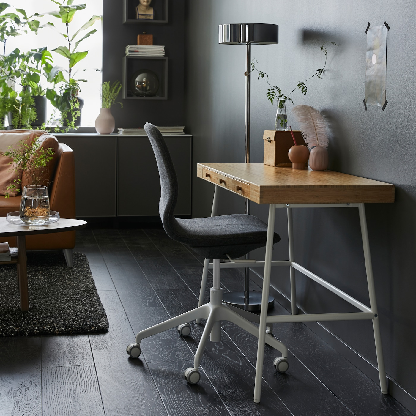 Home office with LILLÅSEN work table, a swivel chair and floor lamp.