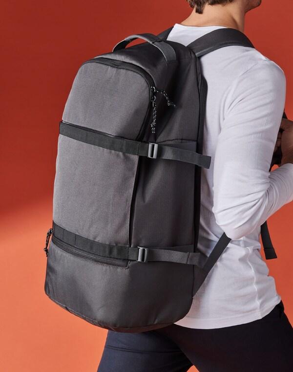 Homem a caminhar com uma mochila VÄRLDENS cinzenta escura às costas, contra um fundo laranja.