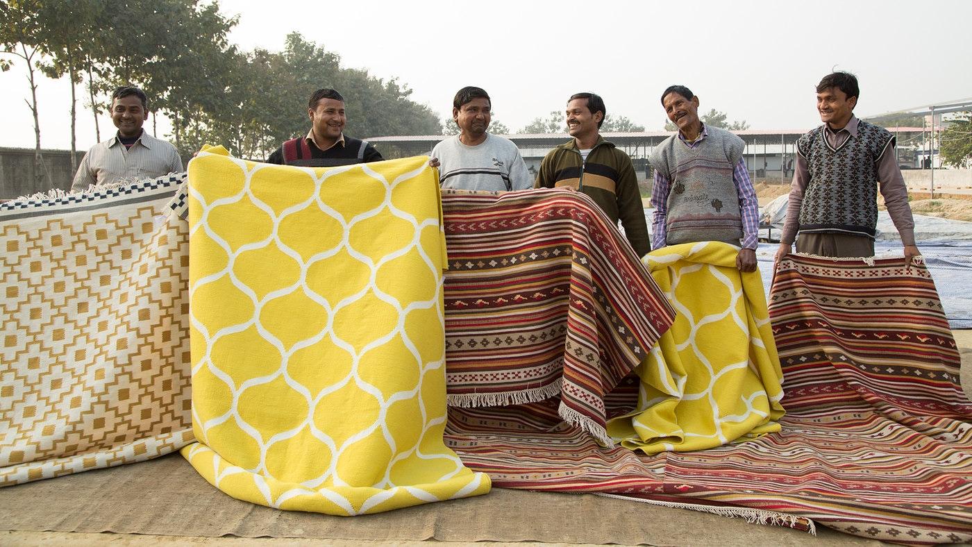 Homem a segurar uma seleção de tapetes tecidos à mão.