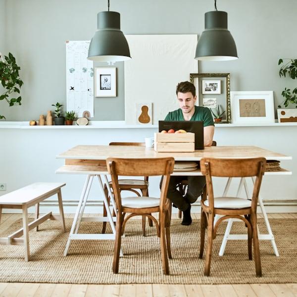 Homem sentado no centro de uma mesa de refeição a mexer num computador, com uma parede verde pastel atrás, dois candeeiros HEKTAR de teto.