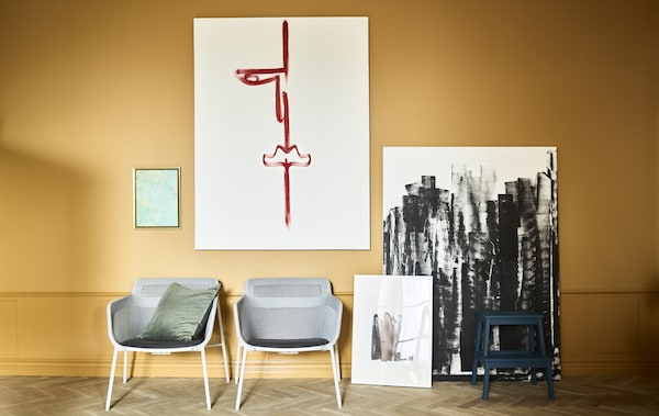 Homemade artwork and two armchairs sits agains an ochre wall.