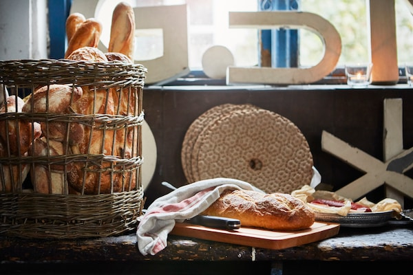 Homemade bread inside a rattan basket and a sliced loaf on the worktop