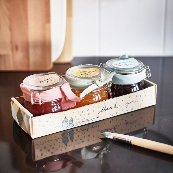 Homemade preserves in KORKEN jars placed in wood box for gifting