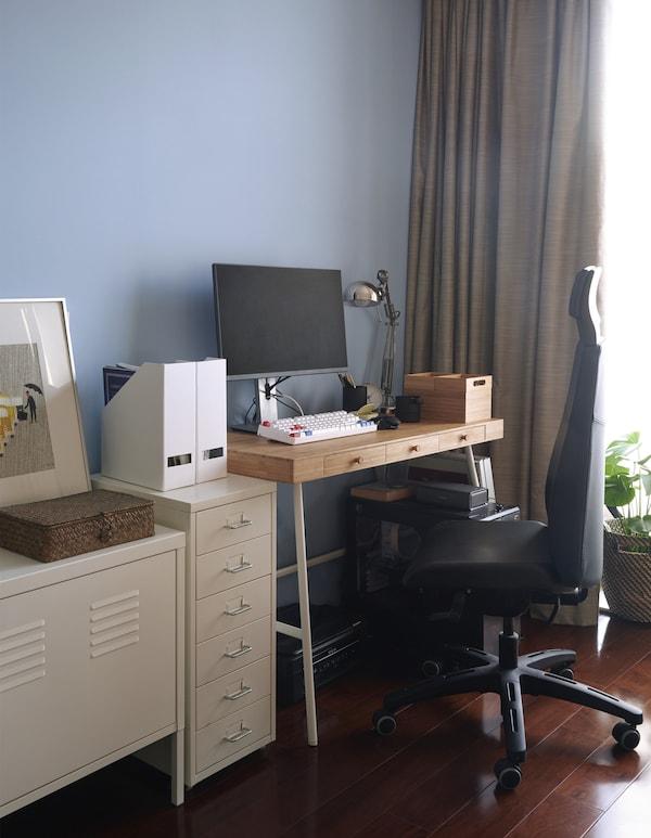Homeoffice vor einer blauen Wand, u. a. mit LILLÅSEN Schreibtisch in Bambus.