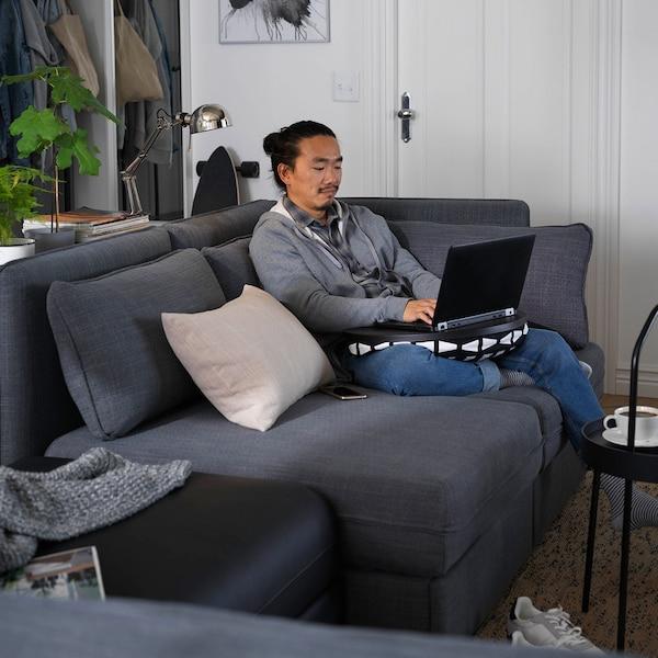 Homme assis sur un canapé gris, travaillant sur un ordinateur placé sur un support d'ordinateur portable.