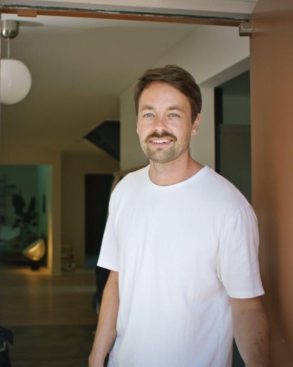 Homme blanc aux cheveux bruns portant un t-shirt blanc debout dans l'entrée d'une maison.
