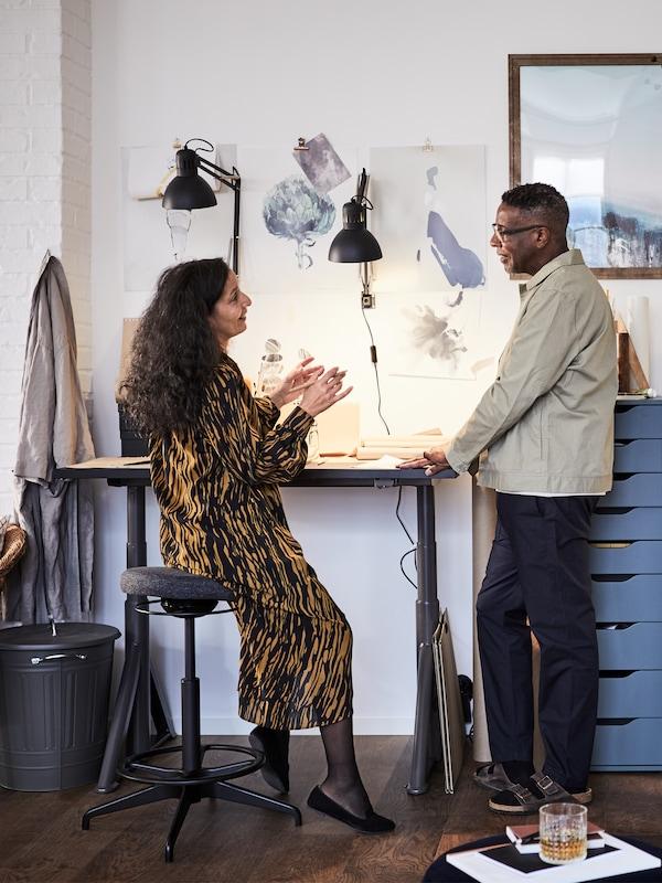 Homme et femme en conversation devant un bureau assis/debout IDÅSEN. La femme est assise sur un tabouret assis/debout LIDKULLEN.