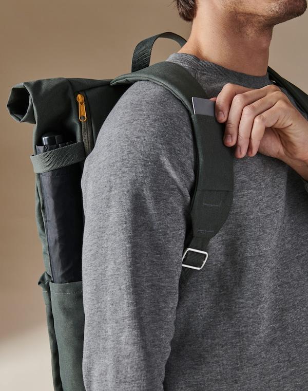 Homme portant un sac à dos vert DRÖMSÄCK, retirant une carte de son emplacement dans l'une des bretelles.