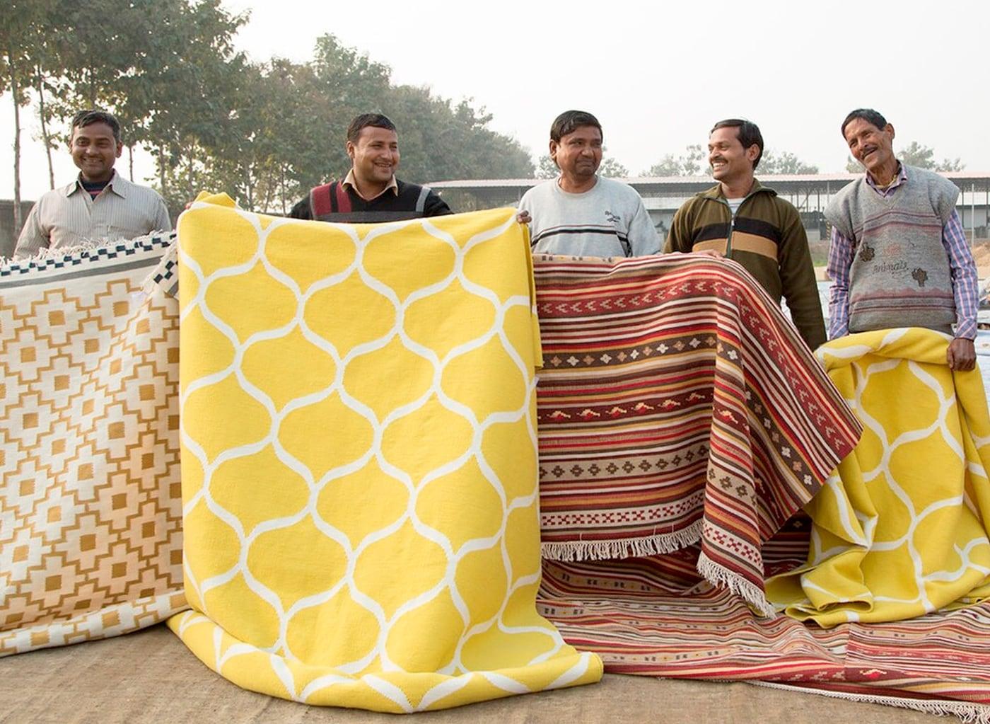 Hommes présentant une sélection de tapis tissés à la main.