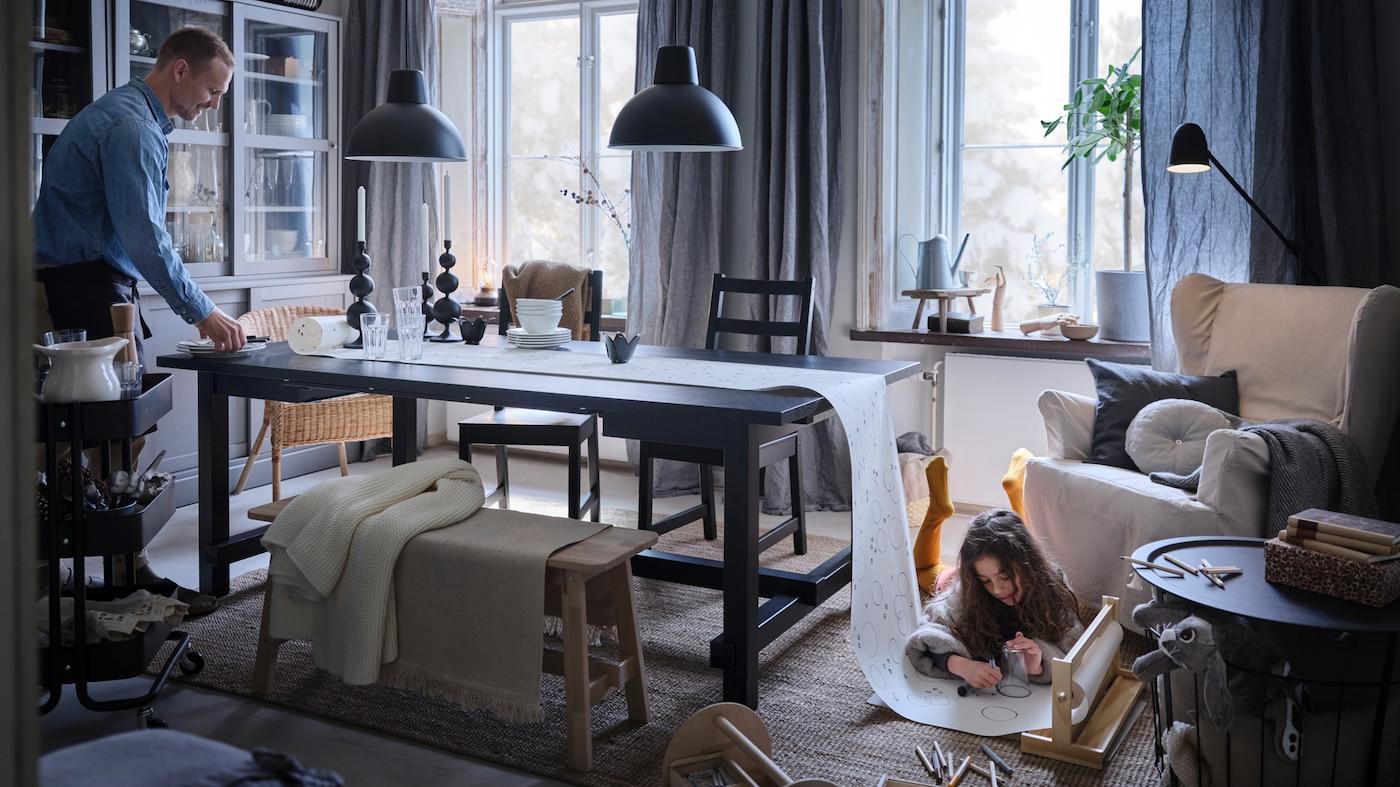 ホリデーディナーのテーブルをセッティングする父親と、その反対側で紙のテーブルクロスに絵を描く娘。