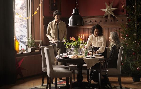 ホリデーの食事を一緒に楽しむために、生花でデコレーションされたINGATORP/インガートルプ テーブルのまわりに集まる3人。