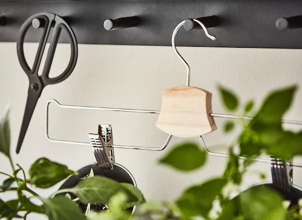 Hormako esekigailutik eskegita dagoen praka/gonetarako IKEA BUMERAN esekileku kromatuaren lehenengo planoa.