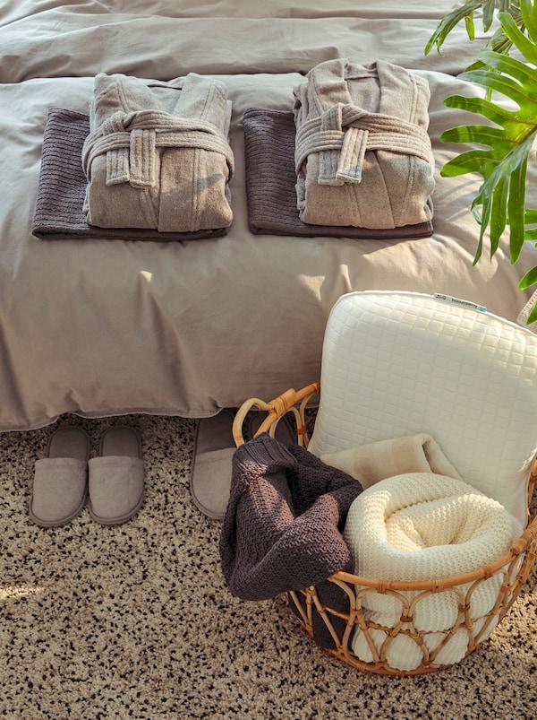 Hotelähnliches Arrangement mit einem gefalteten ROCKÅS Bademänteln und frischen Handtüchern auf einem Bett. In einem SNIDAD Korb finden sich Decken und ein Kissen.