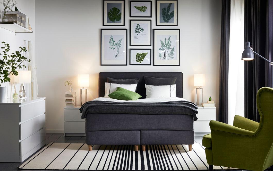 Hotellihuoneessa harmaa sänky ja vihreä nojatuoli. Valkoinen IKEA MALM-lipasto, jossa on 3 laatikkoa. Musta IKEA KNOPPÄNG-julistekehyssetti. Tummanharmaa IKEA DUNVIK-jenkkisänky. Tummanvihreä IKEA STRANDMON-nojatuoli.