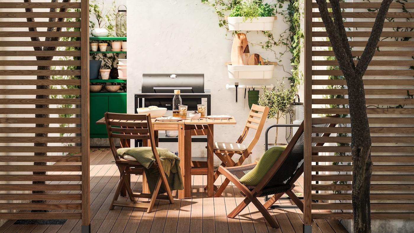 Houten verdelers bieden een kijkje op een terras met houten meubels, houten vlonders, zwarte grill en een groene opberger.