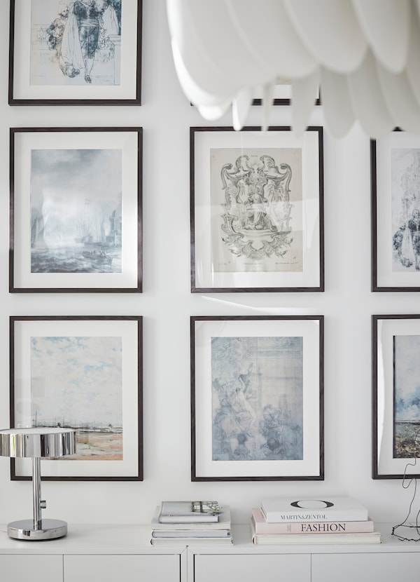 HOVSTA إطارات بنية داكنة من ايكيا مرتبة بشكل متساوٍ على حائط غرفة جلوس أبيض.