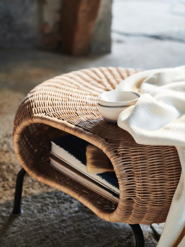 ホワイトのベッドリネンを使ったベージュの布張りベッド。そのそばに、籐製テーブルランプが置いてあるブルーの円形テーブル。