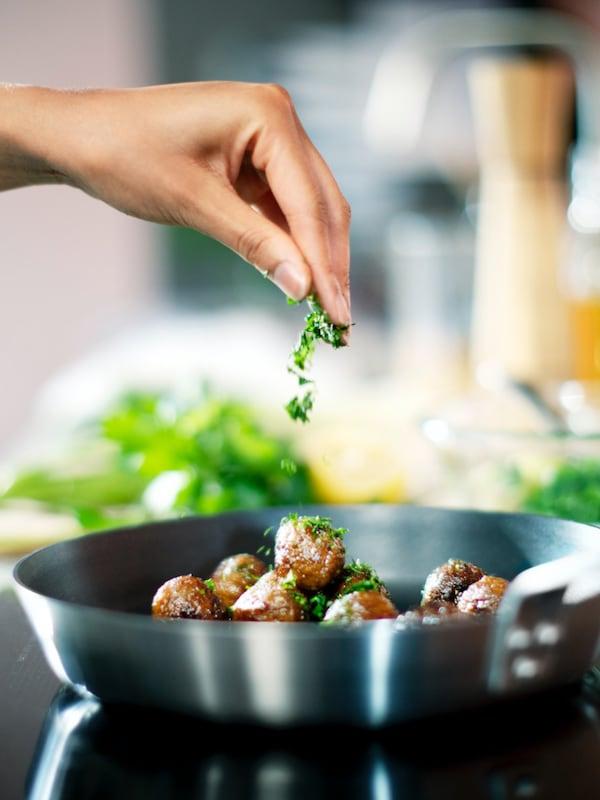 ホワイトのカウンタートップ。緑の野菜をカットしている人物。そばに、フルーツや野菜が入ったガラスと磁器の容器が並んでいる。