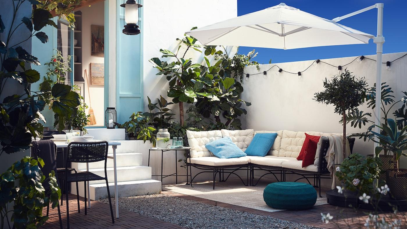 ホワイトのクッションのモジュールソファ、ホワイトのパラソル、ブルーグリーンのプーフ、たくさんの植物がある屋外のパティオ。