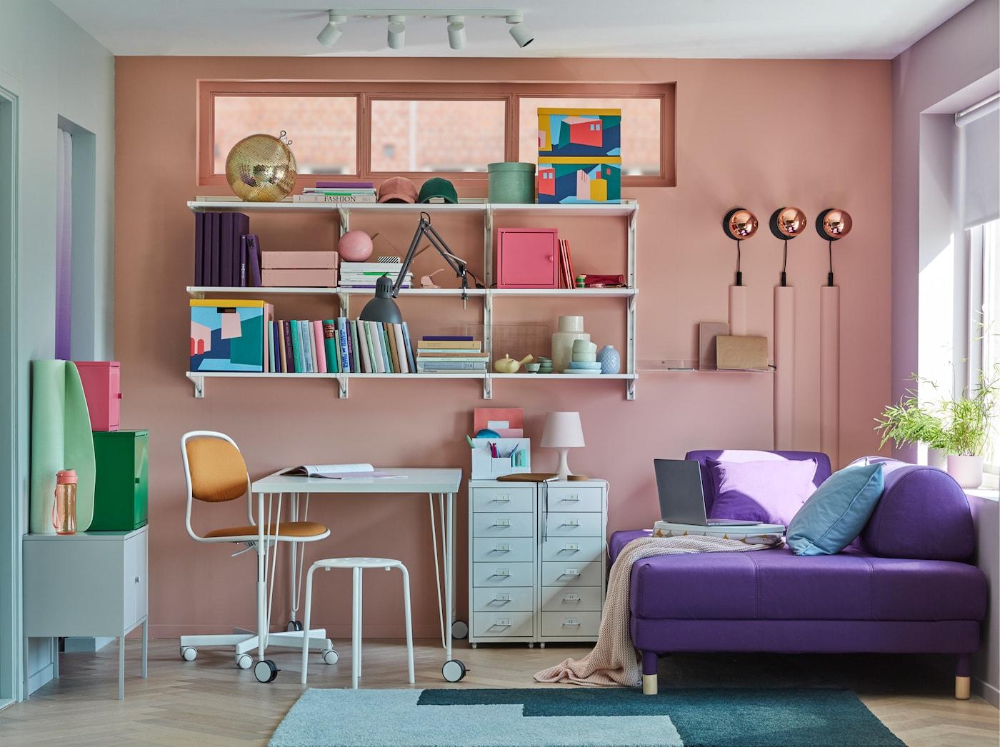 ホワイトのキャスター付きLINNMON/リンモン&KRILLE/クリレ テーブル、ウォールシェルフ、収納キャビネット、ソファベッドがコーディネートされた小さなホームオフィス。