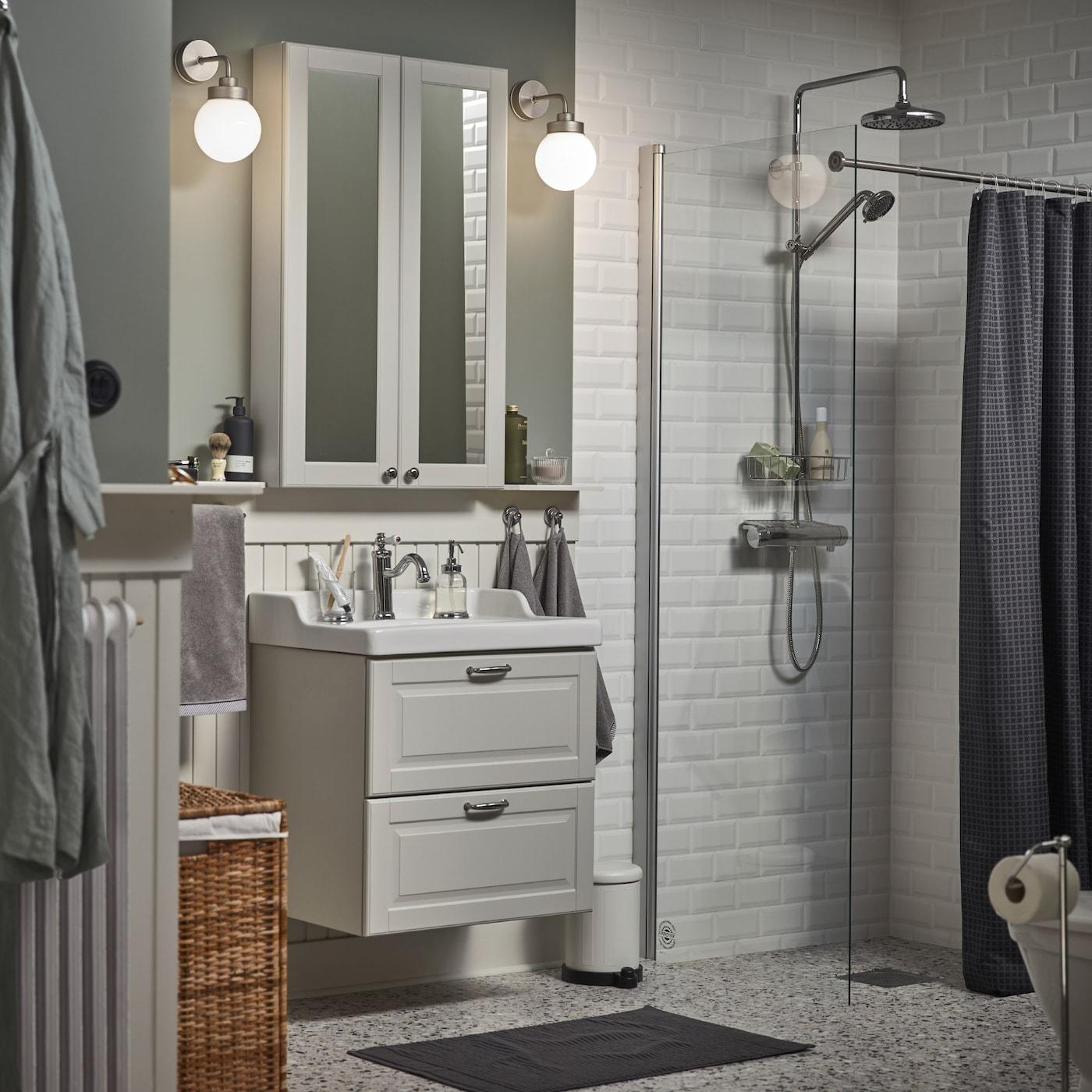ホワイトのミラーキャビネット、グレーの洗面キャビネット、ダークグレーのバスマット、チャコールのシャワーカーテンを配した小さなバスルーム。