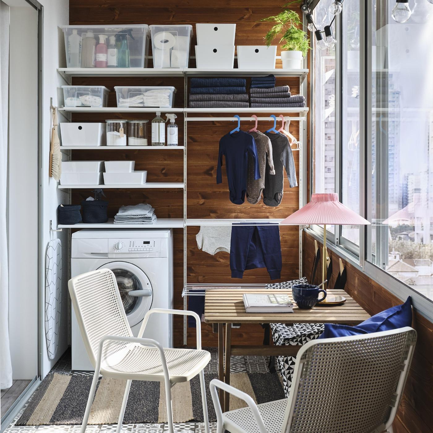 ホワイトの洗濯用収納システム、洗濯機、小さな屋外用テーブル、ホワイト/ベージュのチェア2脚を備えた小さなバルコニー。