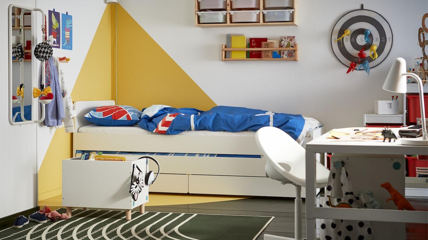 ホワイトとイエローのグラフィックな壁、下に収納が付いたホワイトのベッド、ブルーとレッドのベッドリネンがある子どものベッドルーム。