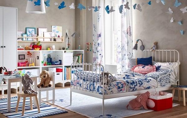 Hravá a usporiadaná detská izba s bielou posteľou, textíliami s kvetinovým vzorom, detským stolom a stoličkami a úložným dielom s knihami, škatuľami a hračkami.