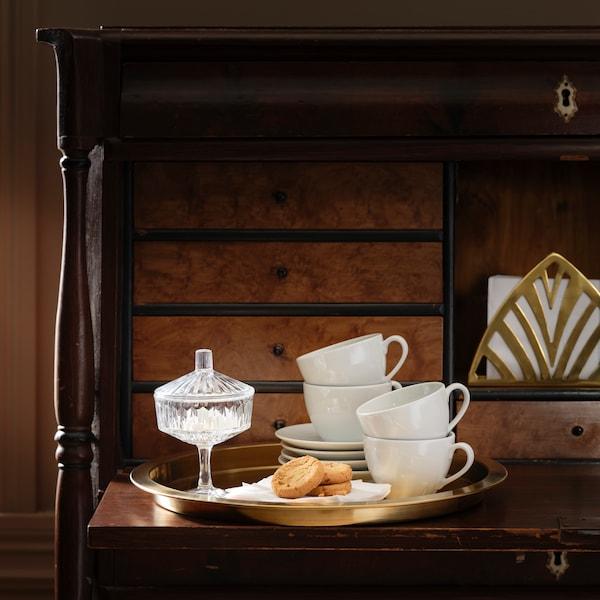 Hrnky a  talíře narovnané na sebe, vedle skleněná cukřenka a talířek se sušenkami.