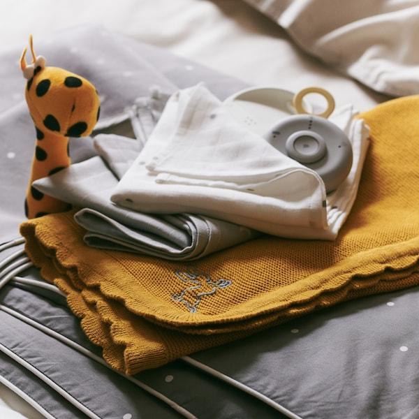 Hromádka dětských textilií včetně tmavě žluté deky SOLGUL apřikrývky do postýlky LENAST, na které leží chůvička UNDVIKA.