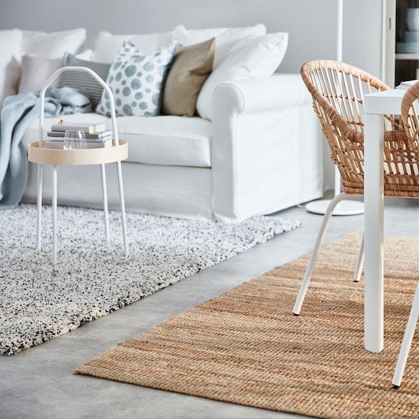 Huone, jossa on valkoinen sohva ja erilaisia tyynyjä, sekä VINDUM korkeanukkainen matto ja LOHALS kudottu matto.