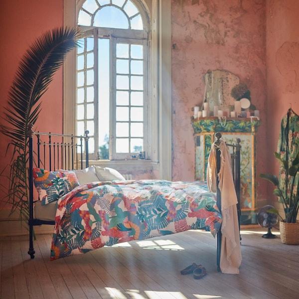 Husa de pilotă SKOGSFIBBLA, cu modelul ei sărutat de soare, e prezentată pe un pat dintr-o încăpere mare, cu ferestre generoase.