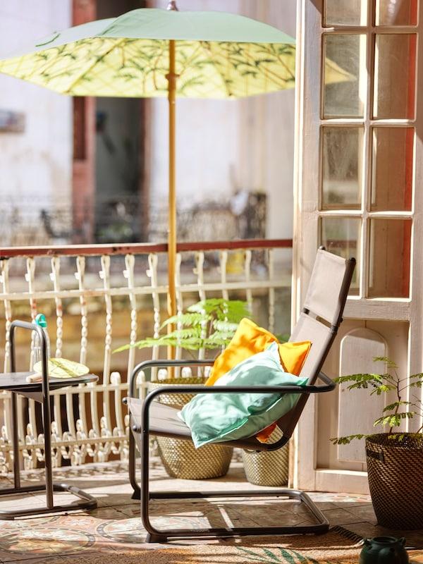 HUSARÖ armchair standing inder parasol.